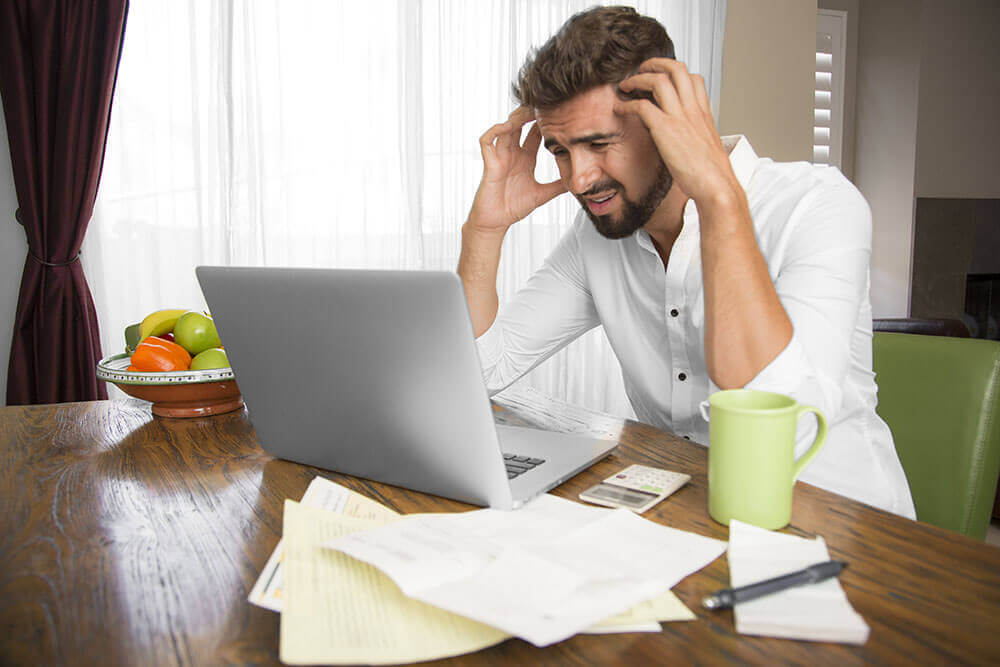 a stressed man on a laptop
